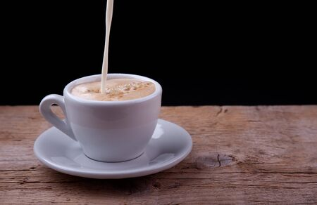 steaming: Coffee with milk pouring down on wooden table