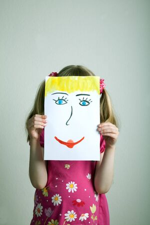 painted face: Little blonde girls holding happy face mask