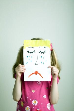 fille triste: Blonds fillettes contenant le masque du visage triste