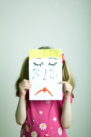 painted face: Little blonde girls holding sad face mask Stock Photo