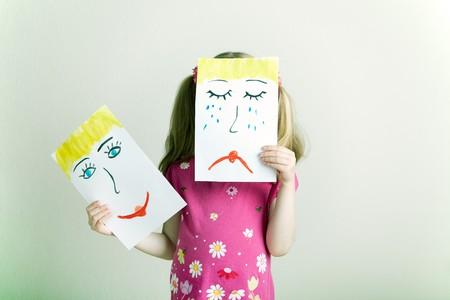 cara triste: Ni�as rubias sosteniendo la cara feliz y triste m�scaras simboliza las emociones cambiantes  Foto de archivo