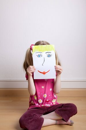 Little blonde girls holding happy face mask photo