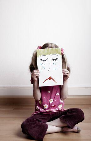 Little blonde girls holding sad face mask Stock Photo