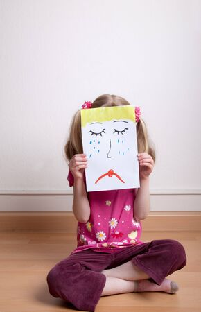 Little blonde girls holding sad face mask Stock Photo