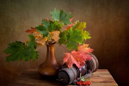 Still Life Autumn concept image with maple leafs and berries photo