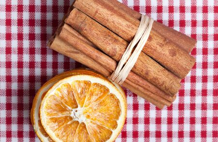 Dried Orange and Cinnamon Sticks on chequered cloth photo