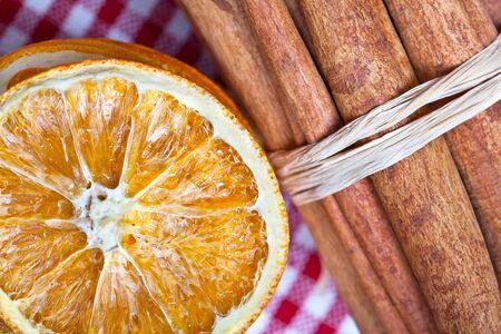 Dried Orange and Cinnamon Sticks on chequered cloth photo