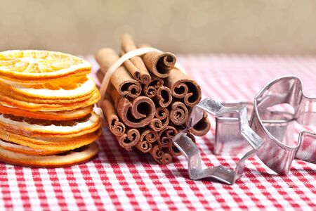 Dried Orange and Cinnamon Sticks on chequered cloth with cookie cutters photo