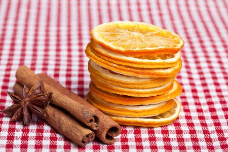 Dried Orange with cinnamon and anise on chequered cloth photo