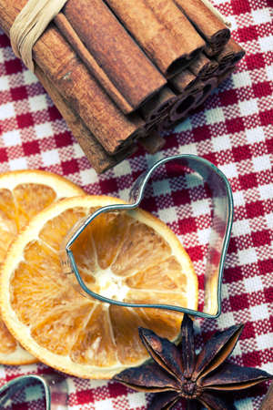 Dried Orange with cinnamon and anise on chequered cloth with cookie cutters photo