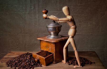 Still Life with Coffee grinder and jointed doll working the mill Stock Photo - 8414999