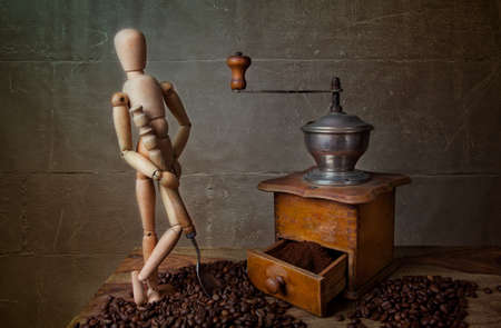 Still Life with Coffee grinder and jointed doll working the mill Stock Photo - 8415001