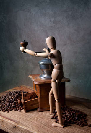 jointed: Still Life with Coffee grinder and jointed doll working the mill Stock Photo