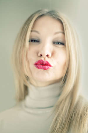 Portrait of a blonde woman pursing her lips photo
