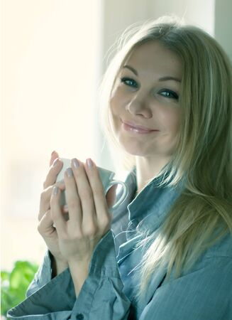 Portrait of a blonde woman holding cup of hot tea photo