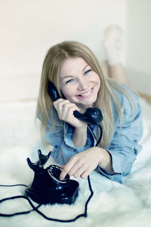 Portrait of a blonde woman lying on bed and making phone call photo