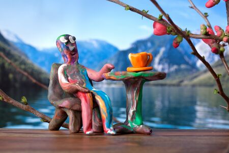 Miniature clay man in cafe with mountain lake view photo