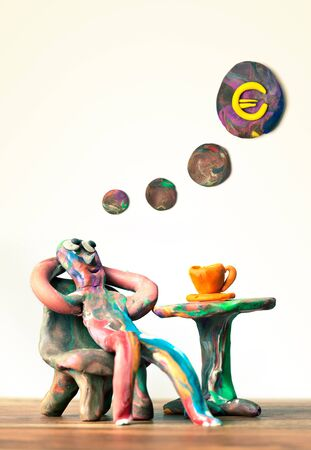 Miniature clay man sitting in cafe dreamin about wealth photo