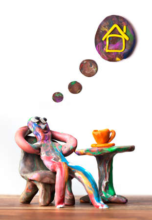 Miniature clay man sitting in cafe dreamin about estate Stock Photo - 8936552