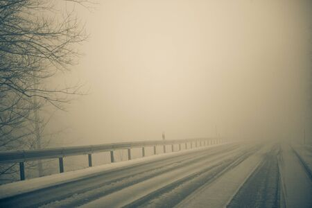 guardrail: Snow and Fog on lonely road in winter