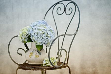 オルテンシア花がレトロな椅子の上に花瓶に古いのある静物 写真素材