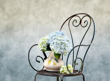 Stilleven foto met Hortensia bloemen op roestig stoel