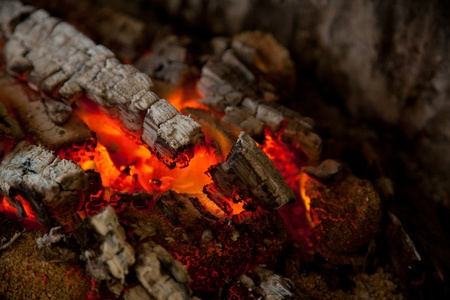 Glowing embers from burned down fire in fireplace Archivio Fotografico