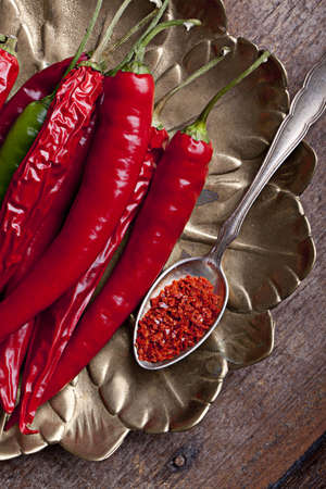 Fresh and grounded chili peppers in red and green photo