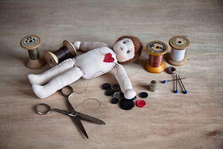 アンティーク ミシン用品でテーブルの上の古い縫いぐるみ人形