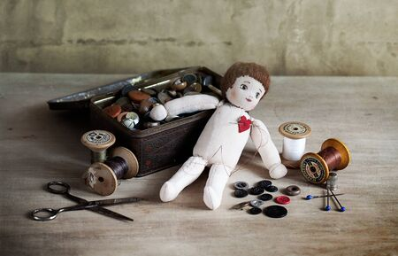 Old Rag Doll on table with antique sewing utensils photo