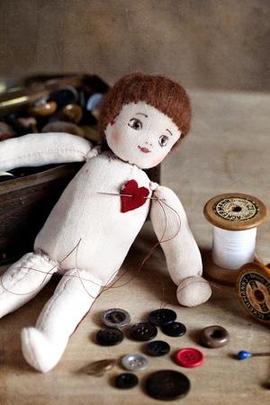 muneca vintage: Rag Doll viejo en la mesa con los utensilios de coser antiguas