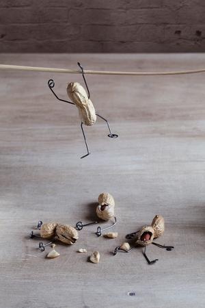 ミニチュア ピーナッツ人々 が彼らのバランスとストローの把握を保持するために試みています。 写真素材