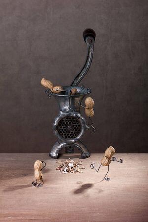 Miniatur mit Peanut Menschen kämpfen gegen ein legte einen Fleischwolf