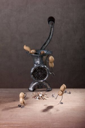 Miniature with Peanut People fighting against being put down a mincer Stock Photo - 11676175