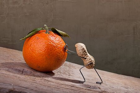 pulling: Miniature with Peanut Man pushing heavy orange up the hill, Sysiphus Concept
