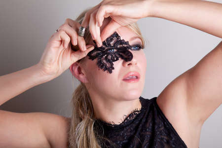 Woman stitching lace mask to her face with needle and thread photo