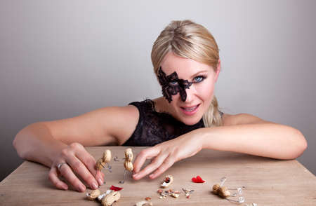 Masked Woman toying with small peanut people models photo