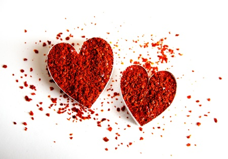 Two hearts filled with grounded red chili flakes photo
