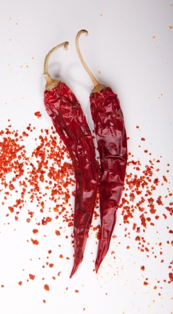 grounded: Two dried red hot chili peppers with flakes of grounded peppers