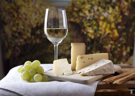 Three kinds of french cheese and a glass of white wine photo