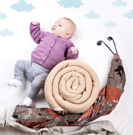 romper: 4 Month old Baby girl riding on Snail Stock Photo