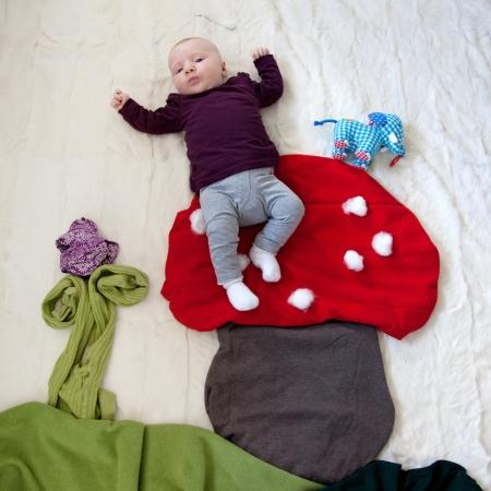 romper: 4 Month old Baby girl sitting on fly mushroom