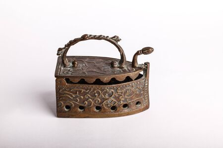 Decorative embossed antique copper iron which was filled with hot coals to enable household staff to do the ironing Stock Photo - 13725172