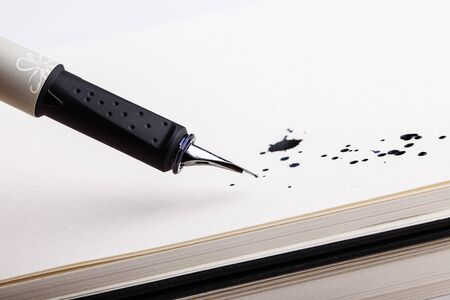 indelible: Two messy black ink splats with fountain pen opened to show the nib on white paper
