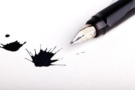 万年筆白い紙の上にペン先を表示するオープンで 2 つの乱雑な黒インク スプラット