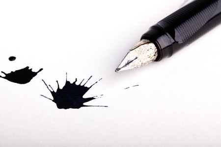 ink stain: Two messy black ink splats with fountain pen opened to show the nib on white paper