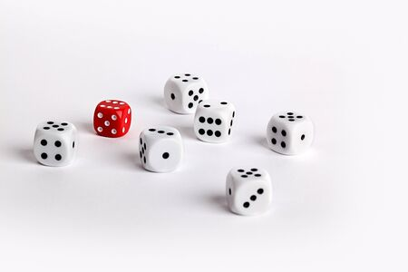 exception: Randomly scattered white dice with one red dice conceptual of individuality