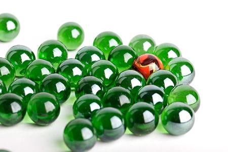 一意性や個性のコンセプトの 1 つのオレンジ色の大理石の緑のガラス玉のグループ