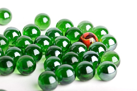 Group of green glass marbles with one orange marble in a concept of uniqueness or individuality Archivio Fotografico