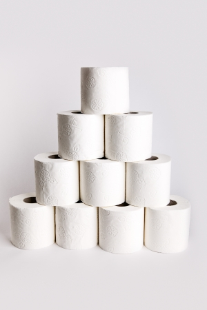 Background still life of a pyramid arrangement of white paper toilet rolls on a white background Stock Photo - 13725119